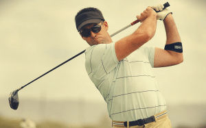 golfer with club and elbow brace